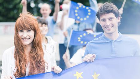 Junge Menschen halten Flaggen der Euopäischen Union in den Händen.