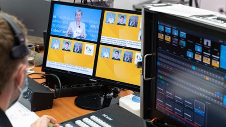 Techniker vor einem Bildschirm, auf dem das Online-Panel zu sehen ist