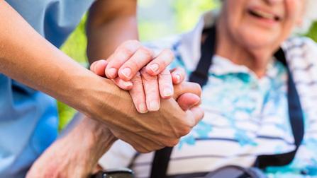 Pflegende Person hält Hand einer betreuten älteren Person.