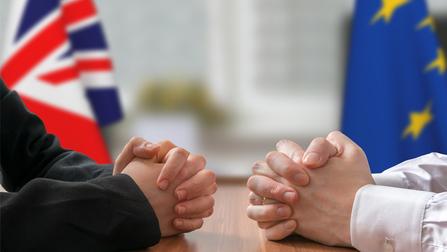 Zwei gegenübersitzende Menschen falten ihre Hände auf einem Tisch zusammen, im Hintergrund ist eine EU und Großbritannien-Flagge zu sehen.