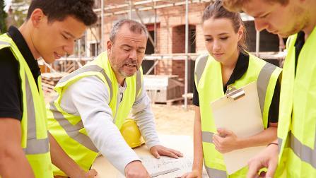 Bauarbeiter mit Auszubildenden auf einer Baustelle