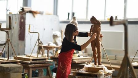 Künstlerin arbeitet im Atelier an einer Skulptur