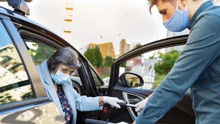 Junger MAnn hilft älteren Dame beim Austeigen aus einem Auto