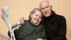 Elderly couple and her holding crutches. Opens page: Reduced earning capacity pensions