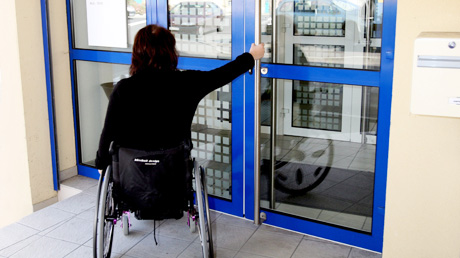 Wheelchair user opening the door of a building