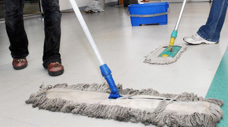 Two custodial workers cleaning the floor