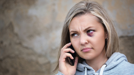A young woman with a black eye is calling someone on her mobile phone. Opens page: Compensation for victims of violent crimes committed in another EU Member State