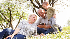 Retirees with their grandchild. Opens page: Pensions from age 67