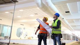 Two construction workers standing in a building, reading the building plans. Opens page: The freedom of movement for workers