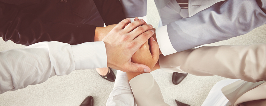 Several business people standing in a circle with their hands on top of each other.