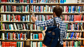 A student standing in front of a bookshelf in a library and taking a book of the shelf. Opens page: Law-making