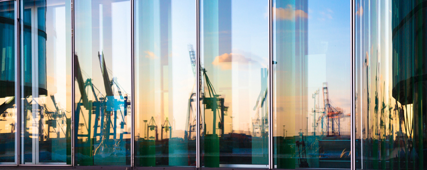 A port reflected in a building's glass facade