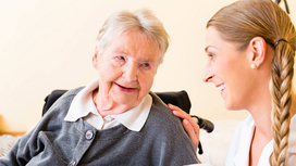 A nurse attentively listens to an elderly woman. Opens page: Strategic social reporting